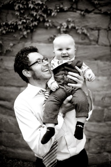 man and baby smile at wedding