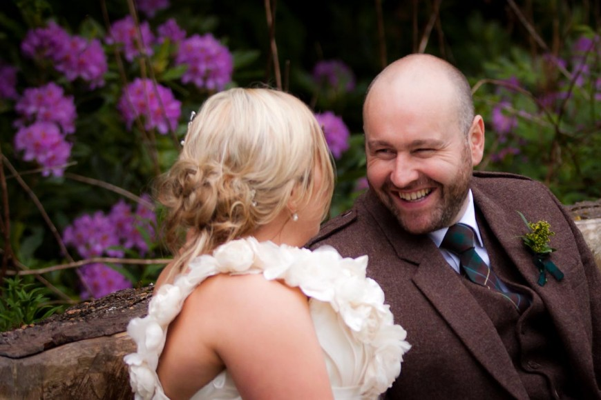 bride and groom outside with purple flowers