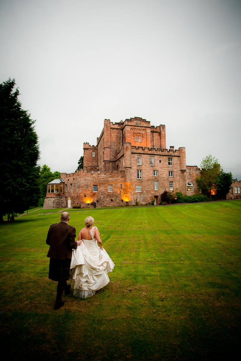bride and groom walk in grounds of dalhousie castle
