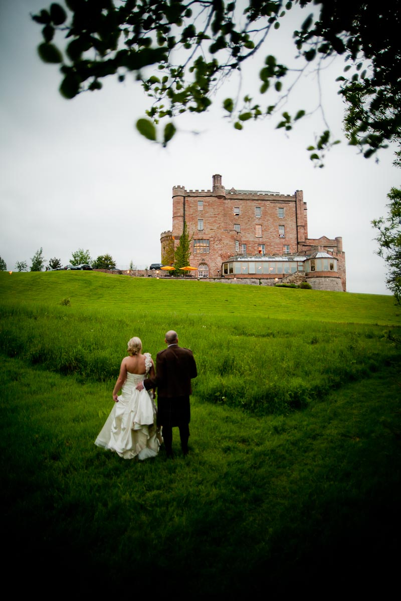 bride and groom admire dalhousie castle