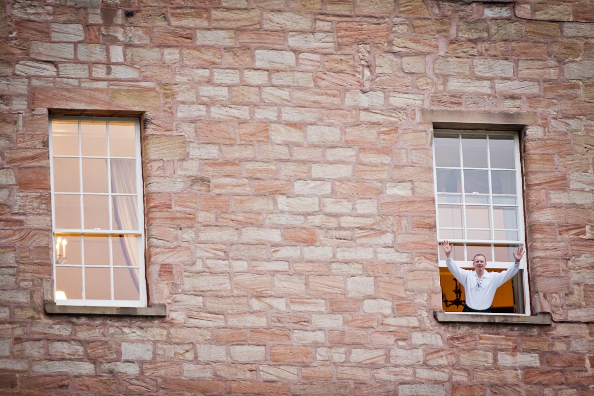 wedding guest waves from window at dalhousie castle.