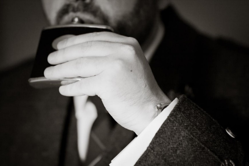 scottish groom swigs from hip flask