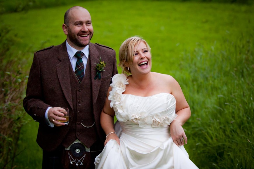 bride and groom laugh as guests wave from window