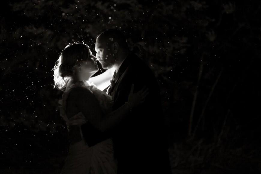 bride and groom kiss in dark