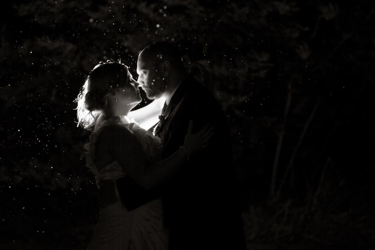 bride and groom kiss in dark