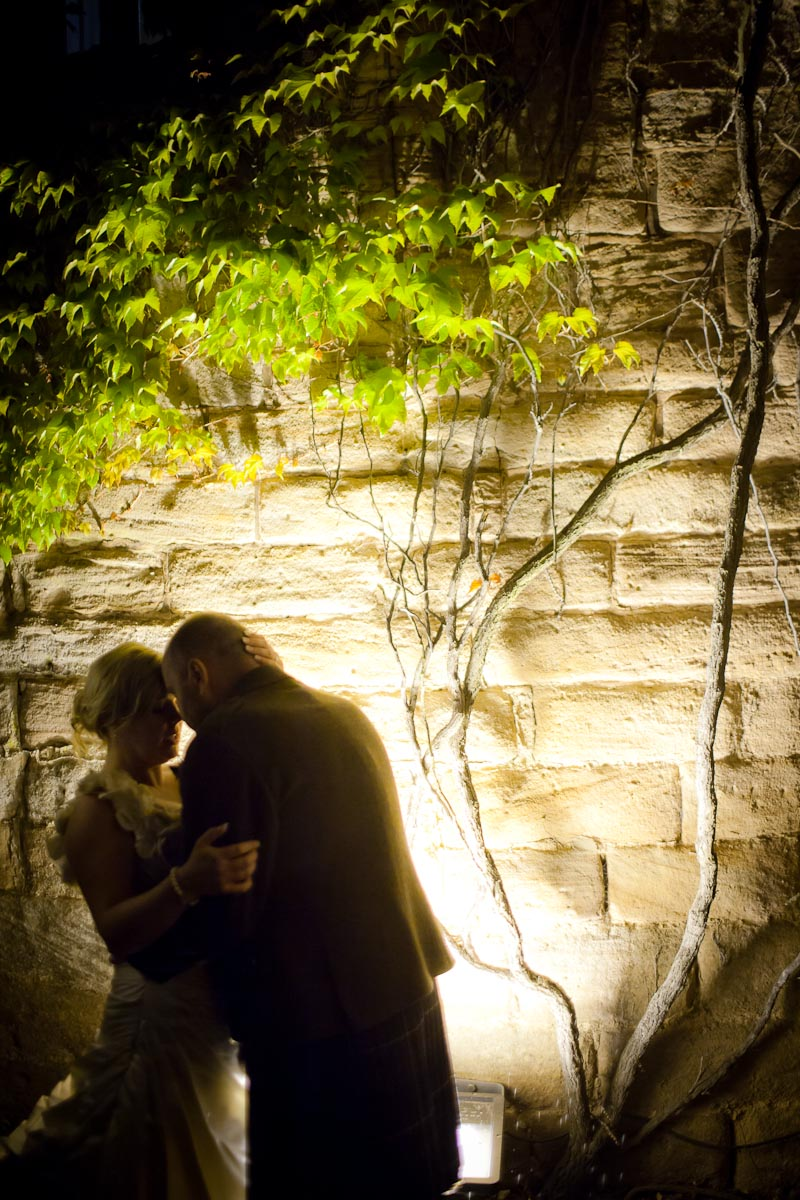 bride and groom outside in dark beside tree