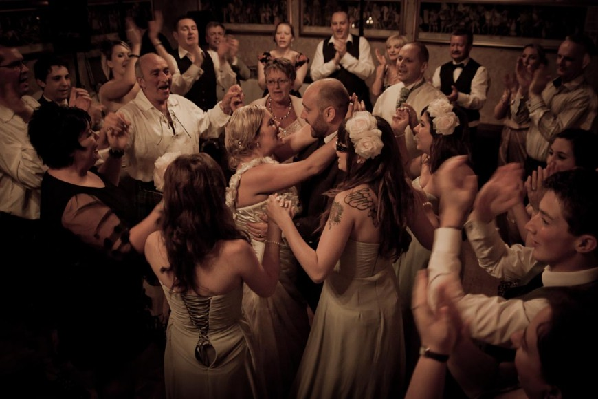 bride and groom dance surrounded by family and friends