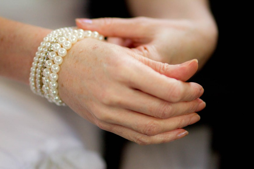 bride adjusts pearl bracelet