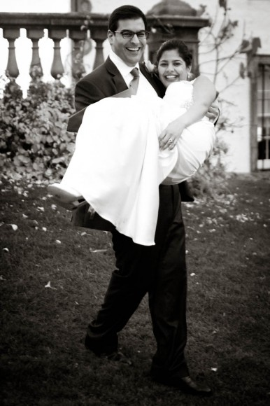 groom carries wife in black and white