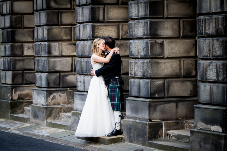 bride and groom kissing outside signet library edinburgh