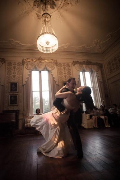 bride and groom dance beneath chandelier at wedding ceilidh at drummuir castle