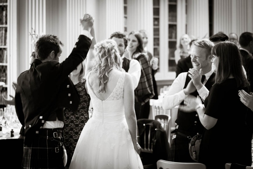 bride and groom cheer at wedding in signet library edinburgh