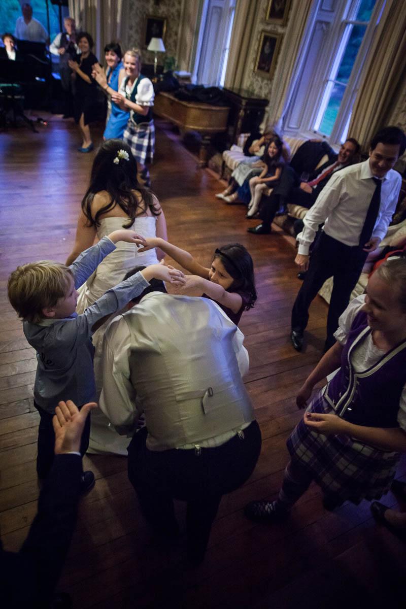 children making archway during ceilidh dancing at wedding at drummuir castle