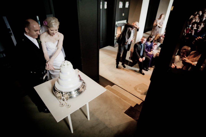 bride and groom cut cake at house for an art lover in glasgow