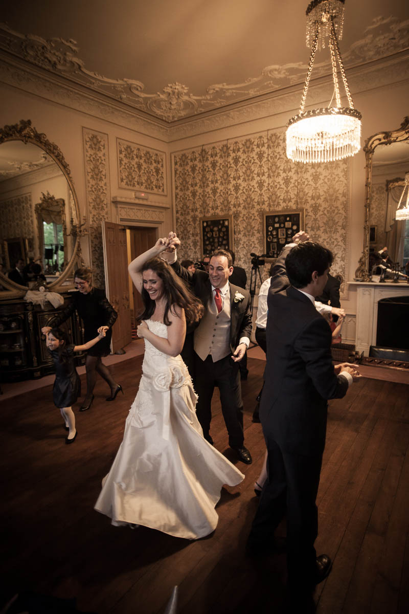 ceilidh dancing beneath chandelier at wedding at drummuir castle