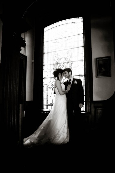 bride and groom by tall window at Solsgirth House