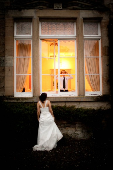 bride outside with groom inside looking out of window