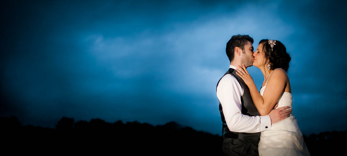 bride and groom kiss outside at dusk
