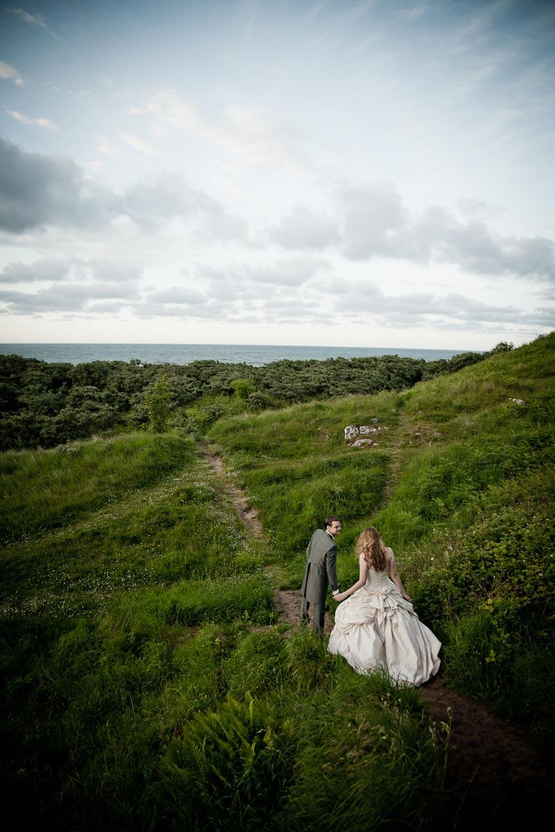 bride and groom on grassy hillside at outdoor wedding