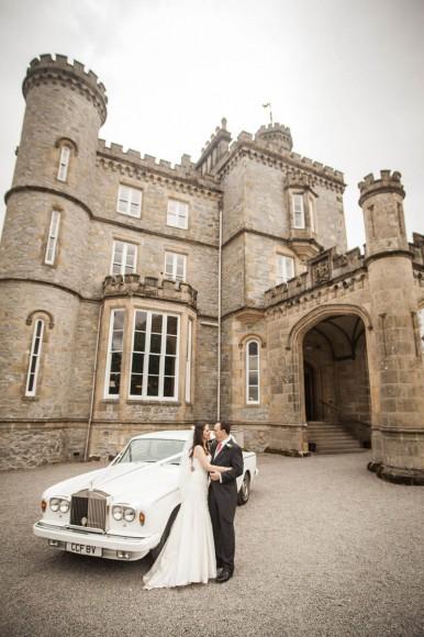 bride and groom kiss by wedding car outside drummuir castle