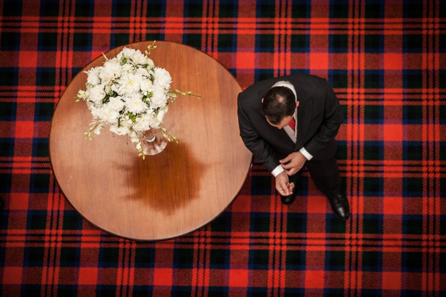 groom and flowers on tartan carpet from above