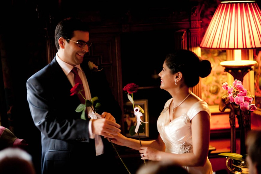 bride and groom exchange red roses