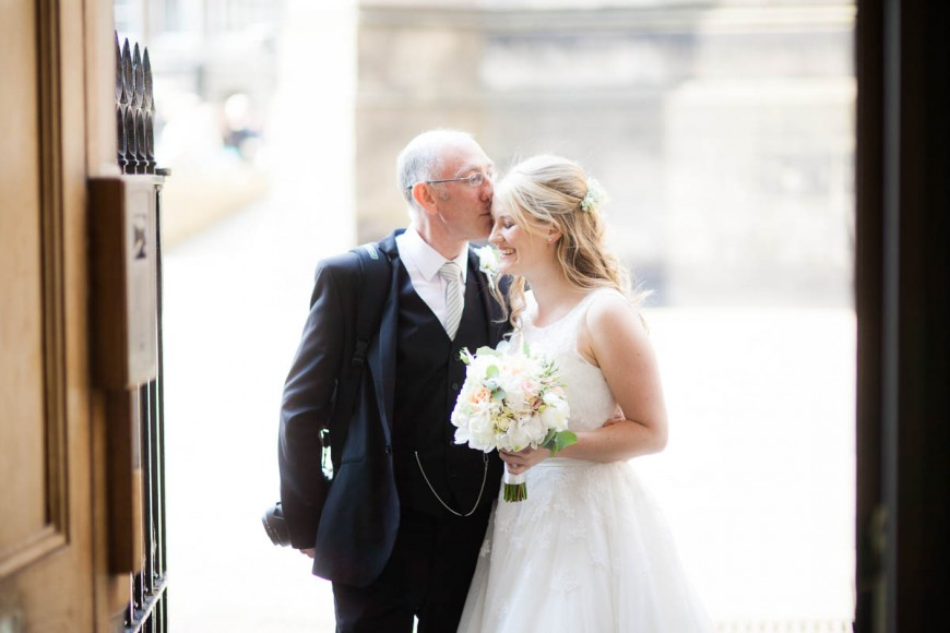 father kisses bride at wedding at signet library edinburgh