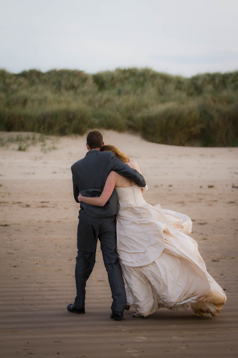 bride and groom blown by wind on beach