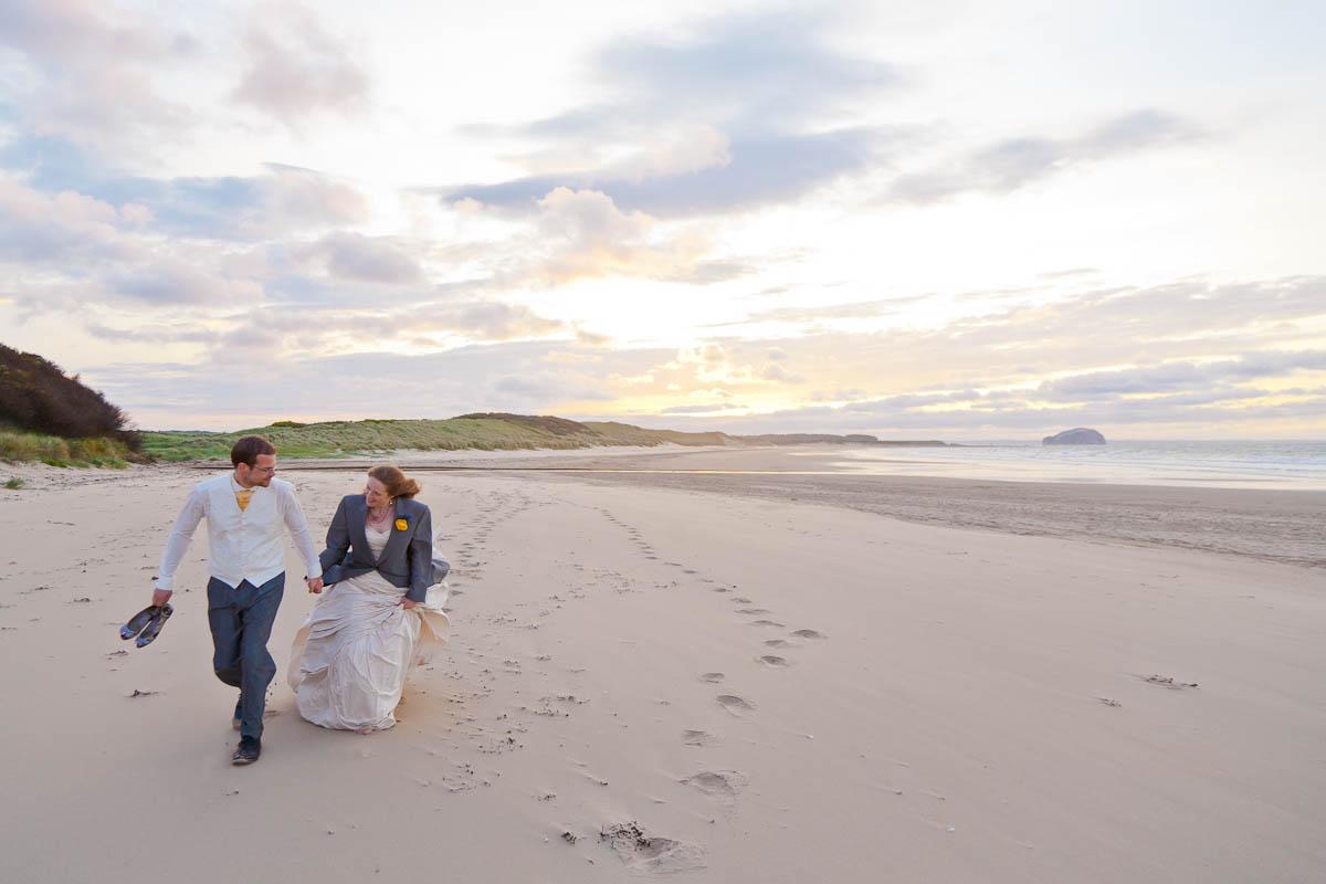 bride and groom make footprints in sand at beach wedding