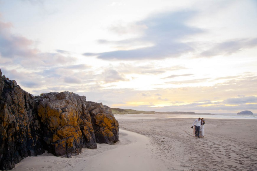 bride and groom walk along beach at sunset