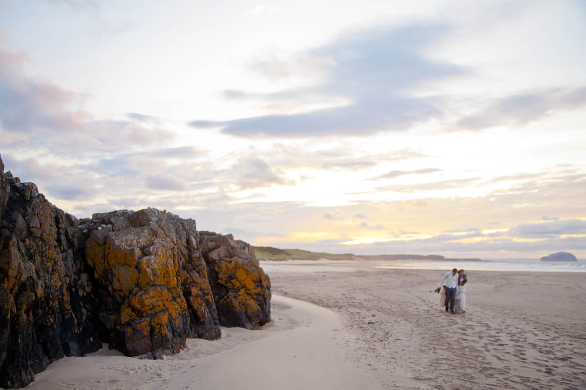 bride and groom walk along beach at sunset