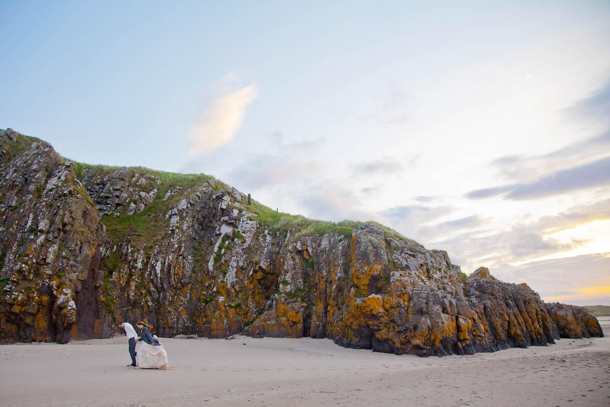 bride and groom walk against wind at beach