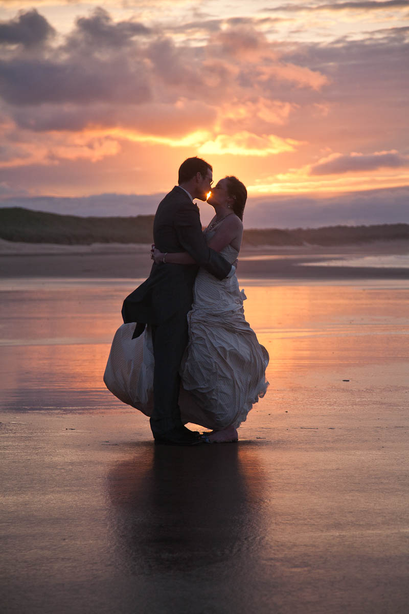 bride and groom on beach at sunset