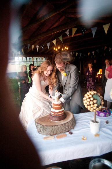 bride and groom vut quirky cake at wedding reception at ravensheugh log cabin