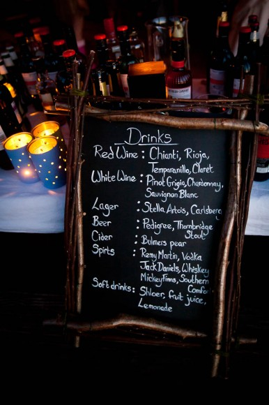 drinks menu on blackboard and candles at log cabin wedding