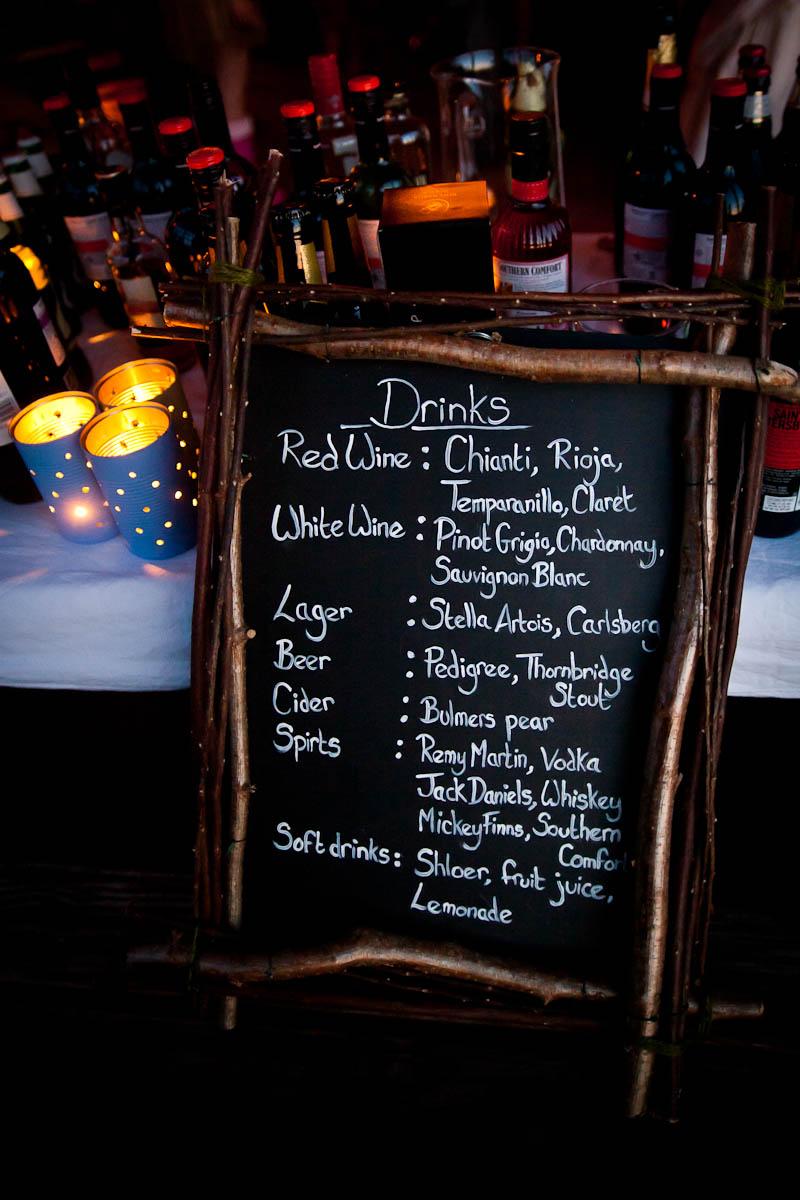 drinks menu on blackboard and candles at log cabin wedding