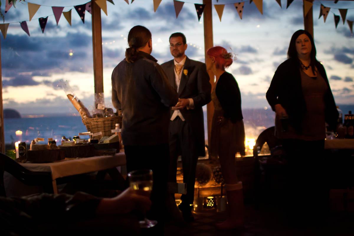 wedding guests talk beneath bunting overlooking beach at ravensheugh log cabin