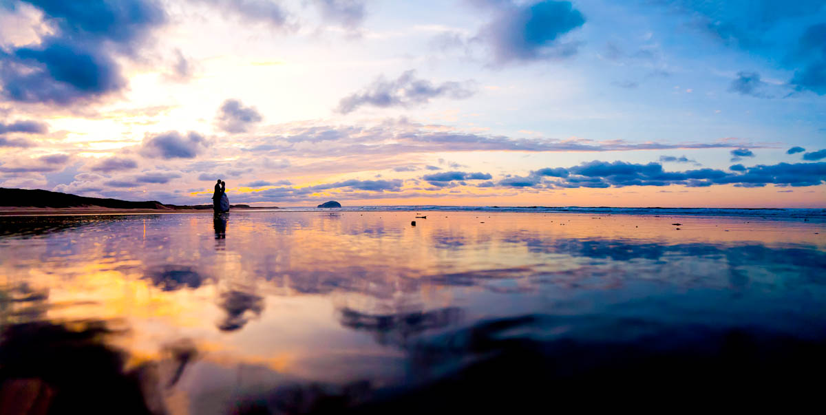 bride and groom on wet beach at sunset
