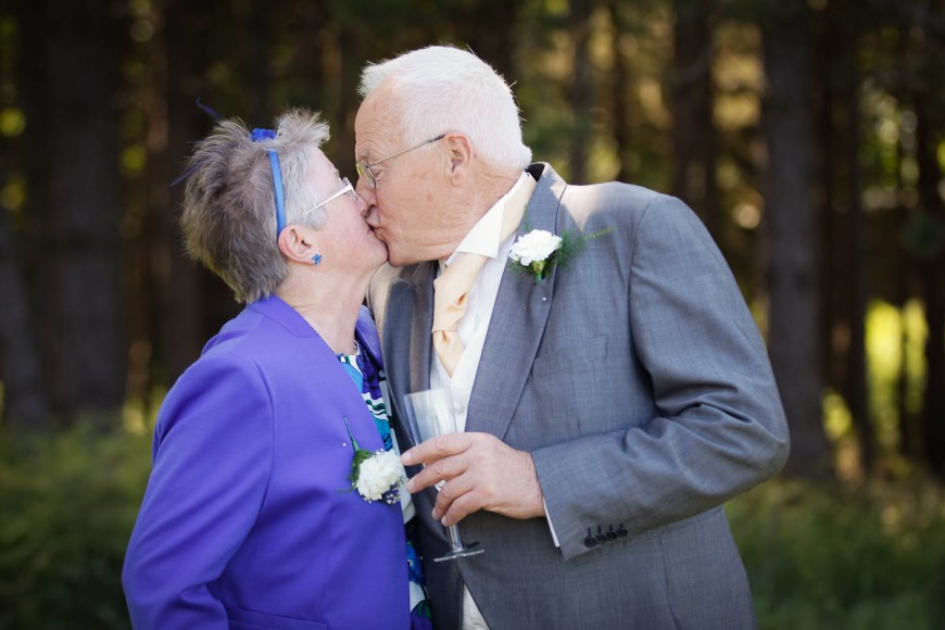 bride's parents kiss at outdoor wedding