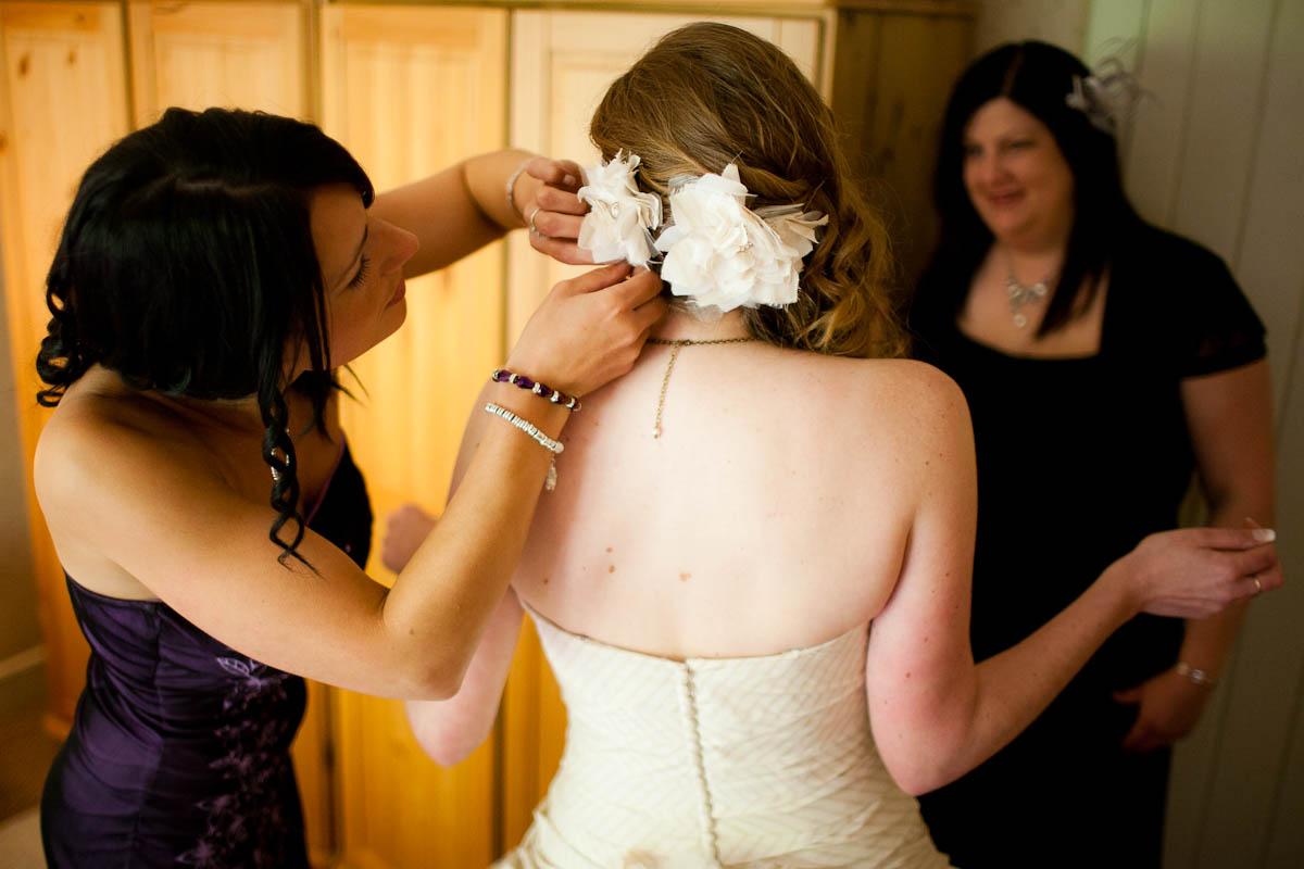bridesmaid fixes bride's hair