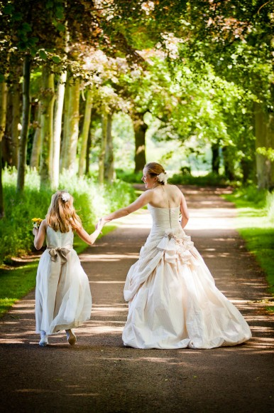bride and flowergirl go to wedding through wood