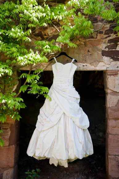 wedding dress hanging up outside bside old wall and tree