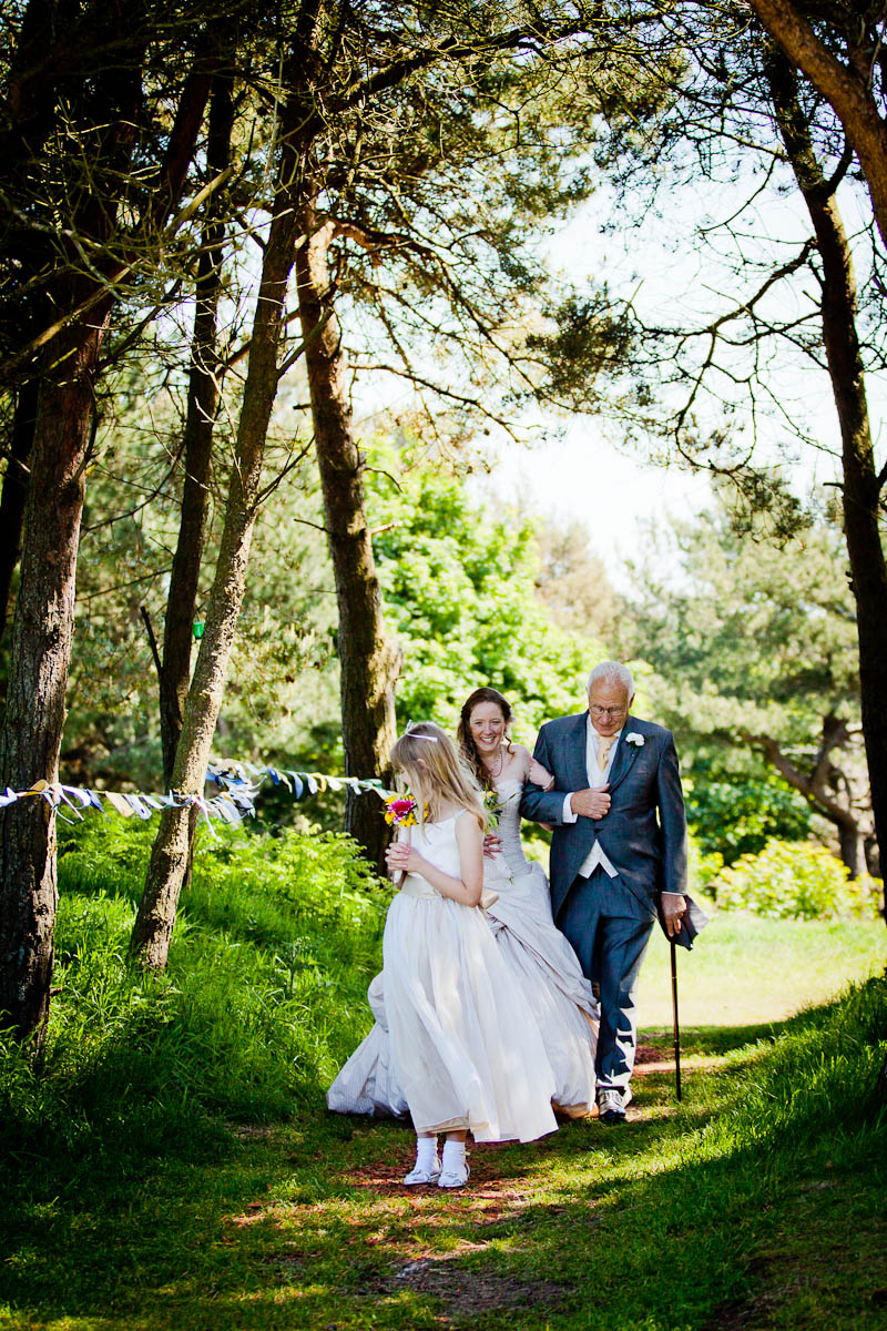 bride arrives at outdoor wedding with father and flowergirl