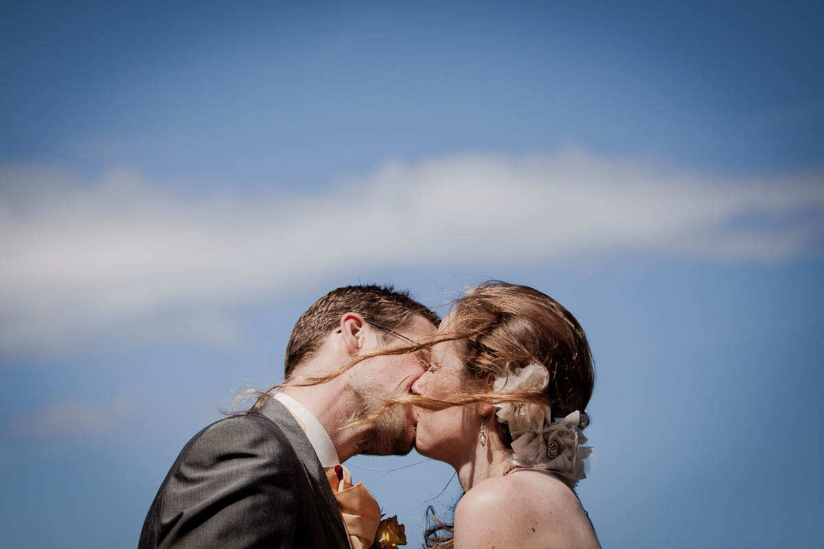 bride and groom kiss at beach wedding on windy day
