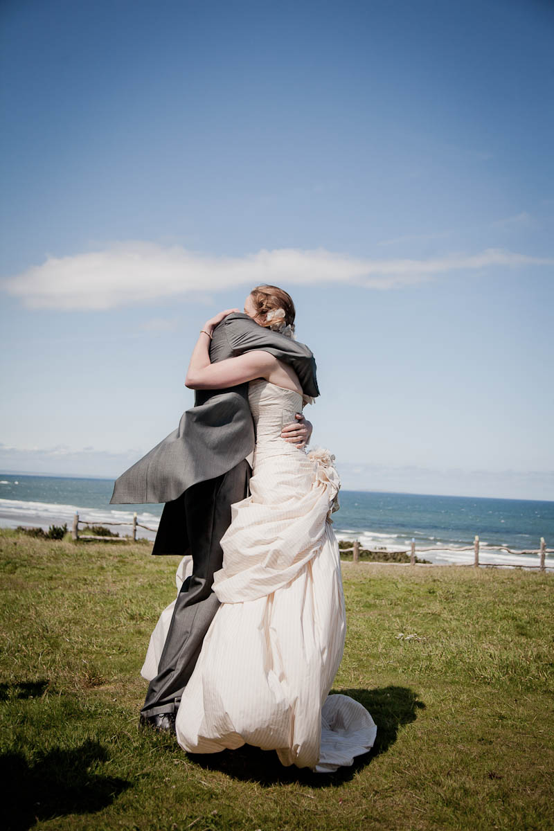 bride and groom embrace at beach wedding