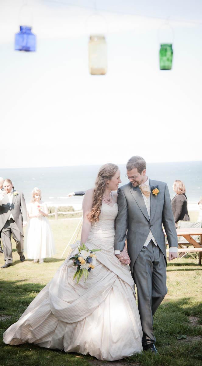 bride ad groom leave wedding ceremony on beach