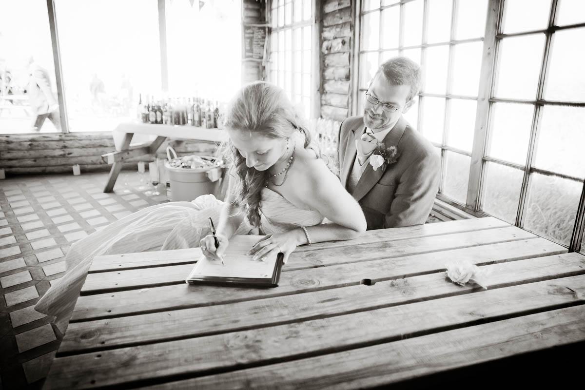 bride and groom sign wedding register at Ravensheugh log cabin