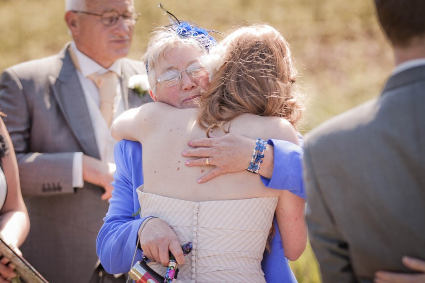 mother hugs bride at beach wedding
