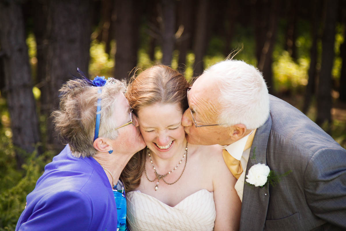 bride kisse by parents at beach wedding