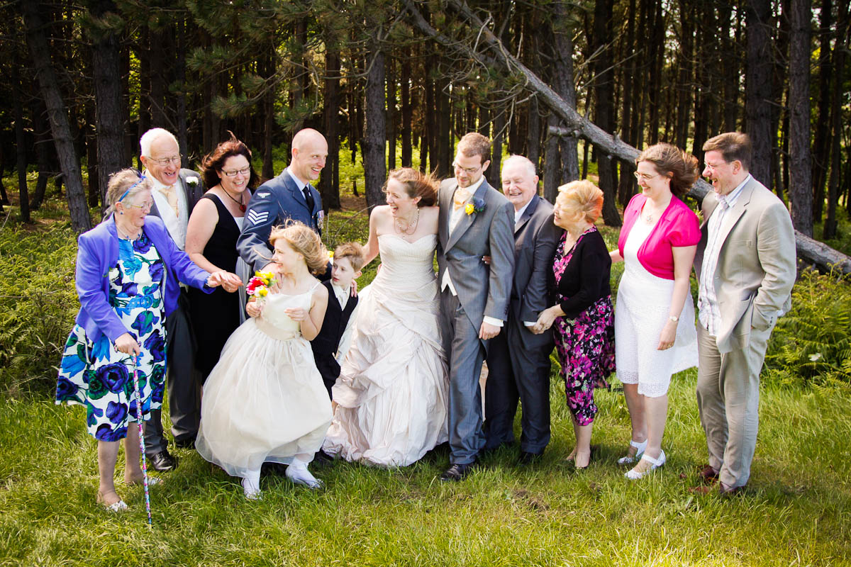 family lines up for photo at outdoor beach wedding on windy day